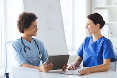 Happy doctors with tablet pc meeting at hospital Royalty Free Stock Photos
