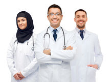 Happy doctors in white coats with stethoscopes Stock Photos