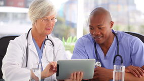 Happy doctors working with a touchscreen. In their bright office stock footage