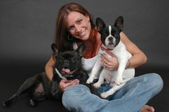 Happy Dogs. Beautiful woman in blue jeans sitting on the floor against a black drop. Woman with her French Bull dogs Royalty Free Stock Photo