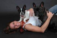 Happy Dogs. Woman holding her French Bull dogs on black background Royalty Free Stock Image