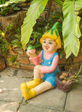 Happy doll in a garden Royalty Free Stock Photography