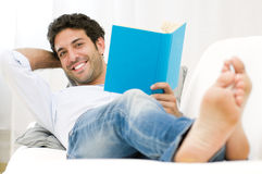 Happy domestic life. Smiling young man reading a book and relaxing on sofa at home Royalty Free Stock Photos