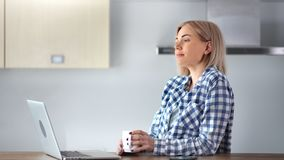 Happy domestic young woman enjoying drinking coffee holding mug at home kitchen. Medium close-up smiling casual female dreaming enjoying weekend using laptop stock footage