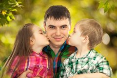 Happy doughter and son kissing their father. Fathers day, family holiday, vacation Stock Photos