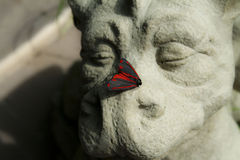 Happy dragon and his Moth. These two subjects work so well with each other. The moth settled on the nose of a delighted-looking statue has an almost whimsical Royalty Free Stock Photos