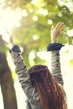 Happy dreadlocks fashionable girl posing in sunny forest stock photography