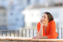 Happy dreamer dreaming looking at side in a town stock image