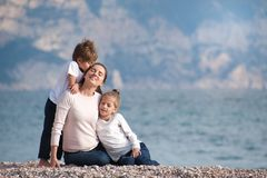 Happy dreaming beautiful family consisting mother and two kids outdoors near sea stock photos