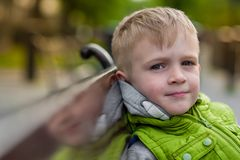 Happy dreaming little blonde boy sitting on a bench. Looking at camera Royalty Free Stock Photo