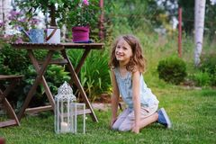 Happy dreamy kid girl playing in summer garden, decorated with lantern light and candle. Blooming flowers on background Stock Image
