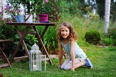 Happy dreamy kid girl playing in summer garden, decorated with lantern light and candle. Blooming flowers on background Stock Photography