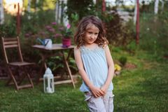 Happy dreamy kid girl playing in summer garden. Decorated with lantern light and candle. Blooming flowers on background Stock Image