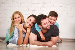 Happy dreamy young couple of parents with their two children at home together. Happy dreamy young couple of parents with two children at home having fun together stock photo