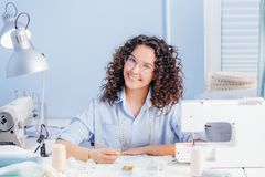 Happy dressmaker embroidering with fashion beads indoors. Stylish accessories. creating beauty stock photo
