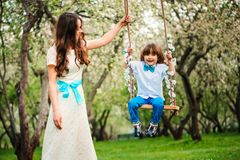 Happy dressy mother and toddler child son having fun on swing in spring or summer park. Wearing bow tie and long lacy dress for birthday or mothers day Stock Photography