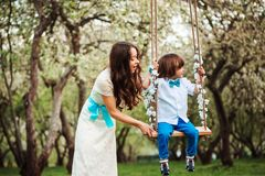 Happy dressy mother and toddler child son having fun on swing in spring or summer park, wearing bow tie and long lacy dress for bi. Rthday or mothers day Royalty Free Stock Images