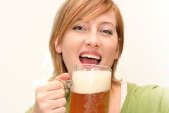 Happy drinking beer. Smiling woman drinking a big glass beer Stock Photos