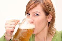 Happy drinking beer. Smiling woman drinking a big glass beer Royalty Free Stock Photography