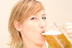 Happy drinking beer. Smiling woman drinking a big glass beer Royalty Free Stock Images