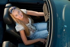 Happy Driver. Young girl driving cabrio car, on sunset light Royalty Free Stock Photo