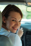Happy driver. Young woman in drivers seat of car stock image