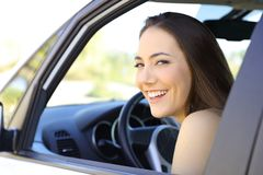Happy driver looking at you inside a car. Happy driver looking at camera inside a brand new car stock image