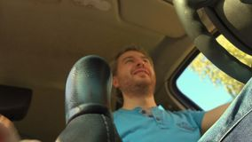 Happy driver shifting the manual stick. Putting car into the first gear. 4K video, low angle view. Happy driver shifting the manual stick. Putting car into the stock video