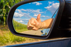 Happy driver. With thumb up in side-view mirror Royalty Free Stock Image