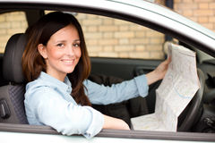 Happy driver. Young woman holding a map sitting in a car Royalty Free Stock Photos