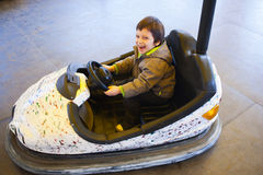 Happy driving bumper car. Happy kid driving bumper car in amusement park Royalty Free Stock Image