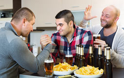 Happy and drunk men armwrestling Royalty Free Stock Images