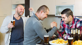 Happy and drunk men armwrestling Stock Images