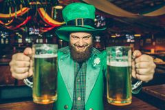 Happy and eacited young man in St. Patrick`s suit in pub alone. He hold two mugs of beer and look on camera. royalty free stock image
