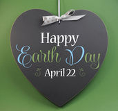 Happy Earth Day April 22, message sign greeting on a heart shaped blackboard. Against a green background Royalty Free Stock Photos