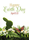 Happy Earth Day, April 22, scene with green moss bunny rabbit, butterfly, ferns and spring blossoms with sample text Stock Images