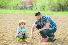 Happy earth day. Family tree. new life. Do everything with love. rich natural soil. Eco farm. small boy child help. Father in farming. father and son planting royalty free stock image