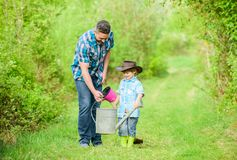 Happy earth day. Family tree nursering. use watering can and pot. Garden equipment. Eco farm. small boy child help. Father in farming. father and son in cowboy stock photography