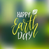 Happy Earth Day hand lettering on blurred background. Vector illustration with leaves for greeting card, poster, etc. Happy Earth Day hand lettering on blurred Stock Photography