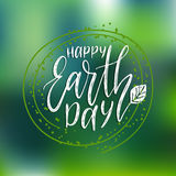 Happy Earth Day hand lettering on blurred background. Vector illustration with leaves for greeting card, poster, etc. Happy Earth Day hand lettering on blurred Royalty Free Stock Photography