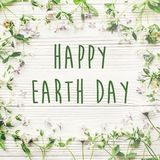 Happy earth day text sign on beautiful lilac and daisy flowers o Stock Images