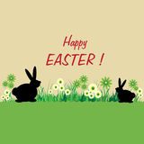 Happy Easter. Abstract colorful illustration with two rabbits standing in grass among flowers and the text Happy Easter written in the middle of the image Royalty Free Stock Image