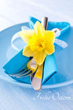 Happy easter. Easter table setting with daffodil and cutlery and german frohe Ostern Stock Photography