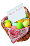 Happy Easter. Wicker basket with Easter eggs and greeting card isolated on a white background Royalty Free Stock Photos