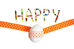 Happy easter. Happy  sign made og pearls decorated with white egg and yellow decoration tape Royalty Free Stock Photo