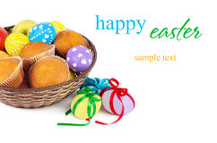Happy easter. Colorful easter eggs with ribbons and basket with cake and eggs on white background Stock Photography