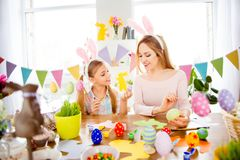 Happy Easter atmosphere! Cute, little, joyful daughter show to c. Reative, funny, pretty, excited mommy her painted, decorated easter eggs, together wearing Royalty Free Stock Photo