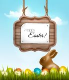 Happy Easter background with chocolate rabbit and wooden sign. Stock Image