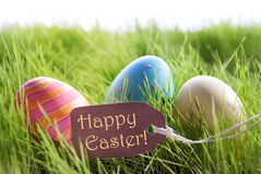 Happy Easter Background With Colorful Easter Eggs And Label. Colorful Easter Background With Three Easter Eggs And Label With English Text Happy Easter On Green royalty free stock photography