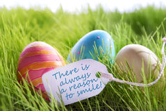 Happy Easter Background With Colorful Eggs And Label With Life Quote. Colorful Easter Background With Three Easter Eggs And Label With English Life Quote There Stock Images